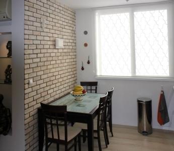עיצוב דירה של אומן, פינת האוכל על רקע קיר לבנים ונישה, עיצוב פנים ופנג שואי, ענבל קרקו
