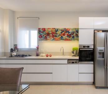 עיצוב דירת קבלן ברחובות לפי הפנג שואי, מטבח לבן עם קלאפה המשלבת ציור של הלקוחה, ענבל קרקו עיצוב פנים ופנג שואי